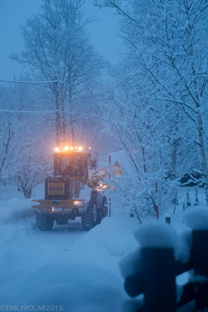 Plow clearing snow in the blue morning dusk of the streets in Niseko Cho, Japan.