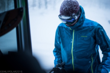 Snowboarder putting gear inside of van after some chilly backcountry riding in Niseko, Japan.