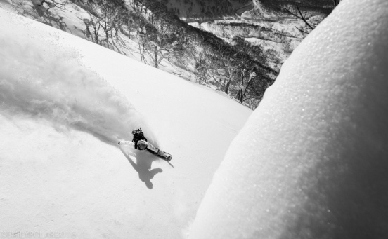 Japanese woman snowboarder ripping up the powder in Nito backcountry on a sunny day in Niseko, Japan.