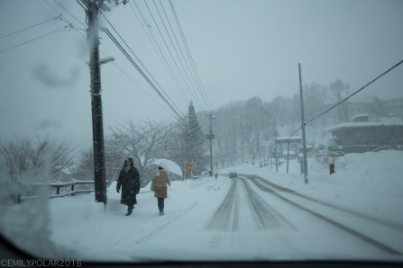 People walking with umbrellas in the winter while a big storm dumps snow in Otaru, Japan.