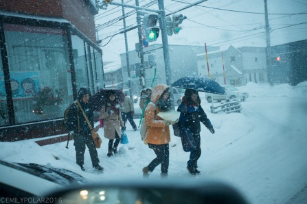 Women crossing street with umbrella in snow storm in Otaru, Japan.