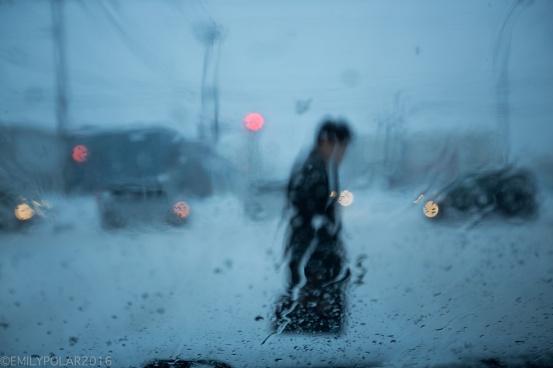 Man crossing street in wet snow seen through a rainy windshield.