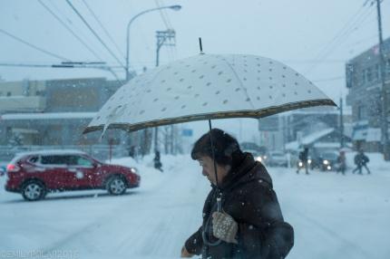Woman crossing street with umbrella in snow storm in Otaru, Japan.