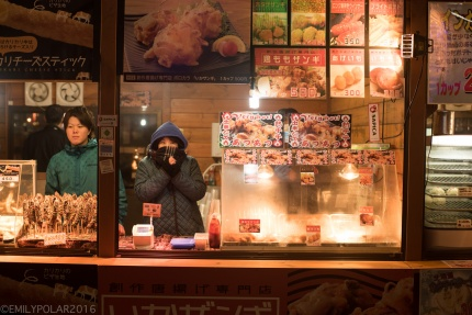 Japanese food stall lit up on cold winters night for the snow festival in Sapporo, Japan.