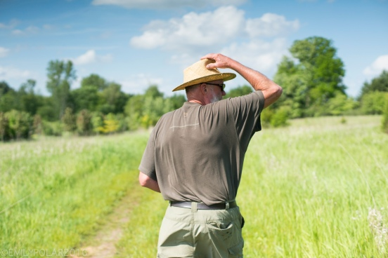 Man adjusts his hat as he walks down a dirt road through green grassy meadow under a blue sky and trees in Wisconsin.