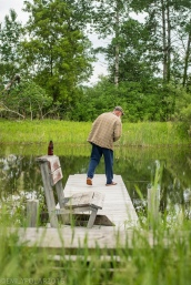 Man standing on his dock at the pond with a beer in Wisconsin.
