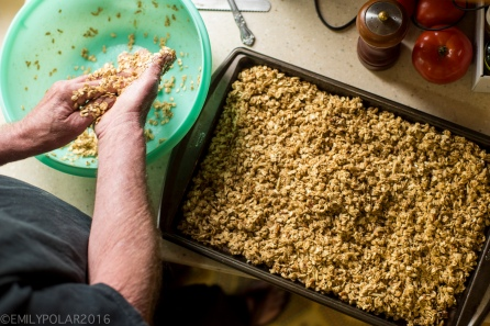 Man making granola spreading the oats onto a baking pan in his kitchen.
