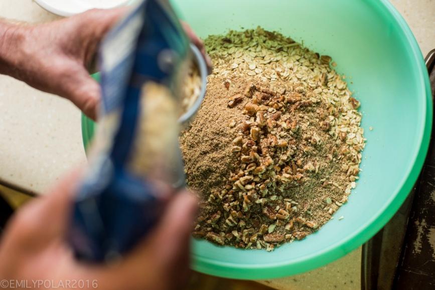 Man making granola mixing ingredients in a big green tupperware bowl in his kitchen.