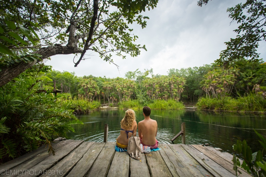 Young couple sitting on a wooden dock at the waters edge of Crystal Cenote surrounded by the lush green jungle of Tulum, Mexico.