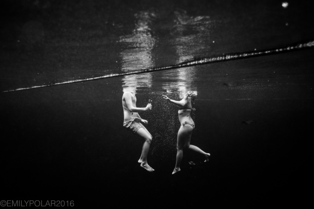 Man and woman swimming in the deep waters of Cenote Escondido in Tulum, Mexico.