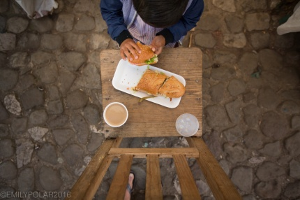 Young Mexican boy eating his breakfast sandwich at the market in San Cristobal, Chiapas, Mexico.
