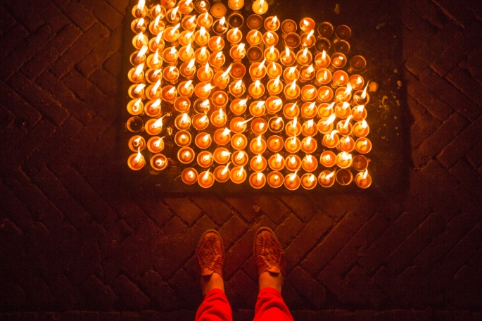 Full tray of butter lamps on a tray on the ground with my feet and red pants for Diwali festival of lights in Boudha, Nepal.