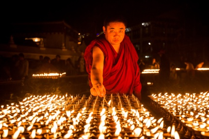 Buddhist monk lighting butter lamps at Boudha Stupa for Diwali festival in Boudha, Nepal.