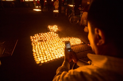 Man taking photo of butter lamps with his smart phone at Boudha Stupa, Kathmandu, Nepal.