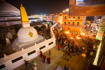 Tourists and locals circumambulating the Boudha Stupa at night surrounded by tables of butter lamps for Diwali festival of light.