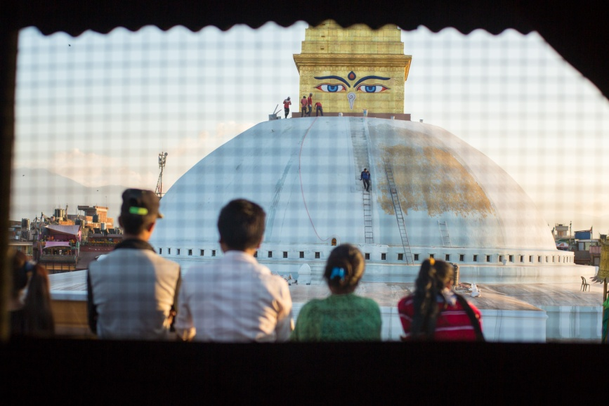 Tourists and locals taking photos of the Boudha Stupa in Boudhanath, Nepal.