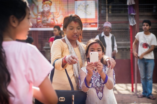 Nepali mother with daughter taking a selfie with phone in the streets of Patan, Nepal.