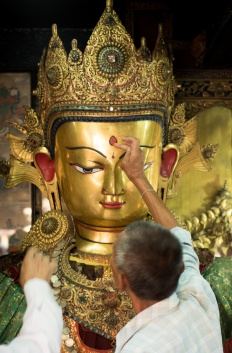 Nepali men decorating a golden Buddha head at the Golden Temple in Patan, Nepal.