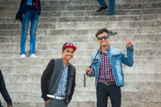 Nepali tourists taking photos with their smart phones and selfie sticks at the Peace Pagoda in Pokhara, Nepal.