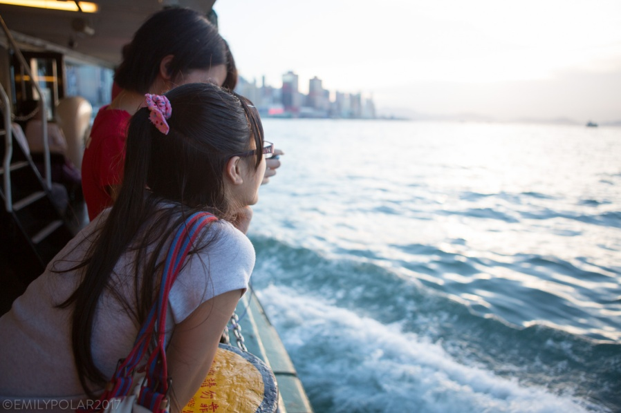 Young Chinese girls look out at water on boat to Central Hong Kong.