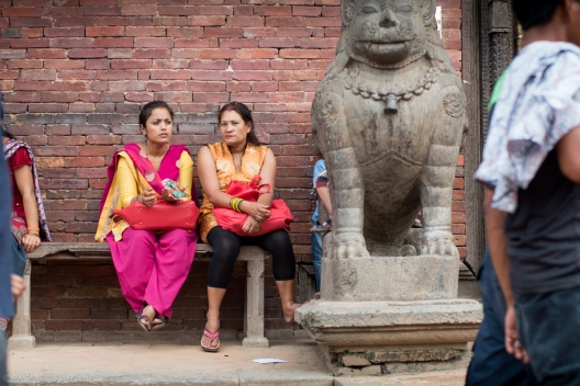Nepali women sitting at the entrance of a temple in Patan enjoying a snack in their colorful sari's.