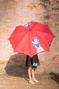 Young Nepali girl standing with her red umbrella in the sun in front of a brick wall in Patan, Nepal.