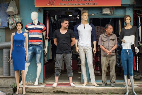 Men shop owners stand next to manikins at the store front of their clothing store in Patan, Nepal.