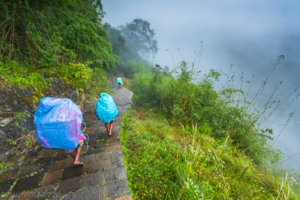 The end of August can still feel like monsoon season in some regions of Nepal. Here porters carry supplies covered in large plastic rain bags to teahouses serving the trekkers in the Annapurna Conservation area.