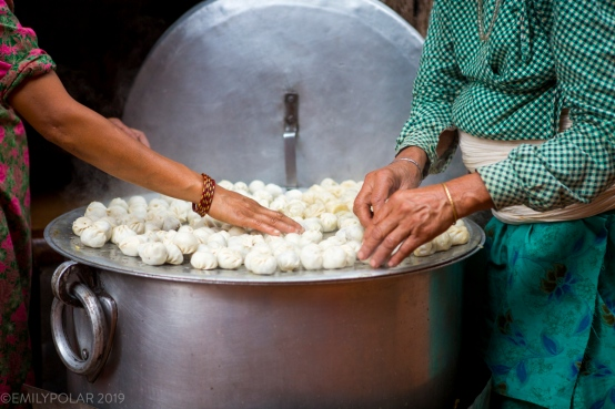 Nepali women steam a large batch of buffalo momos/dumplings on a flat top double boiler outside of their small restaurant in the streets of Bhaktapur, Nepal.