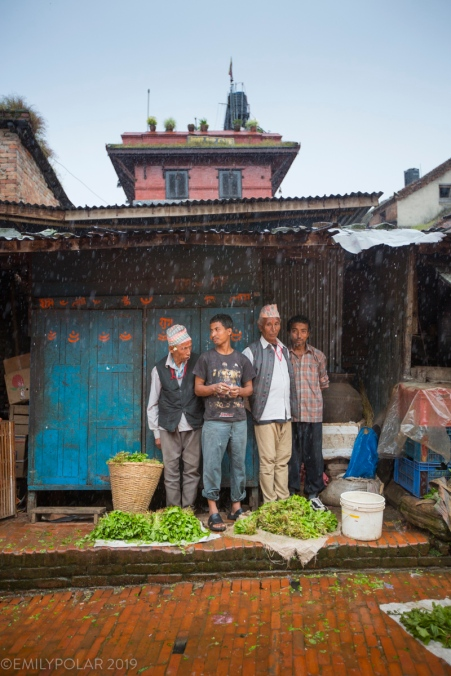 Nepali men and shop keepers in Bhaktapur stand under roof in the rain.