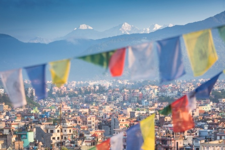 The urban Kathmandu valley seen through prayer flags hugged by the green hillsides of Shivapuri national park far below the snow covered peaks of the Langtang region.