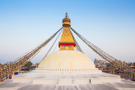 In the low light of dusk a man walks clockwise around the upper level of the Boudha Stupa in Boudhanath, Kathmandu.