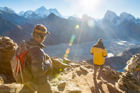 Two men hiking down from the top of Gokyo Ri for a sunrise view over Everest in the Himalayas.