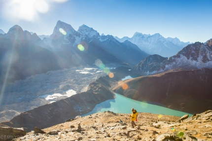 Hiker walking down from the top of Gokyo Ri after sunrise. Gokyo village and Gokyo lake below Ngozumpa glacier to the west.