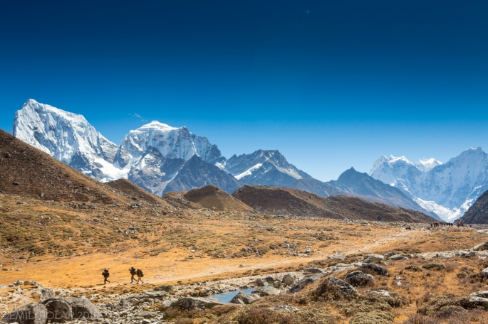 Group of porters walk ahead of group with large packs on trail leading to Gokyo Lake in the Everest Region with Cholatse rising high in the Himalays of Nepal.