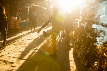 A Nepali boy plays outside his fathers shop in the days last light among the many vendors in the busy streets of Thamel.