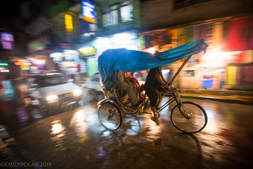 A cycle rickshaw driver petals his passengers through the rain past illuminated store fronts in the heart of Thamel, Nepal.