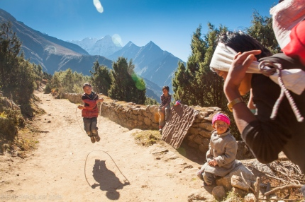A young Nepali girl jumps rope outside her home as a porter comes into the frame. The trails here in the Khumbu have been used for centuries for transporting goods long before trekking became an attraction in Nepal.