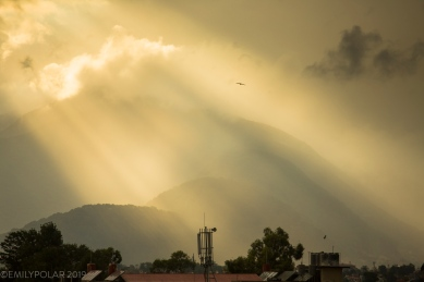 Rays of light shine through monsoon clouds seen from a rooftop in Kathmandu valley.
