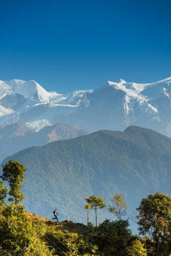 View of a mountain ridge trail from Sarangkot with the backdrop of huge Himalayas in Nepal.