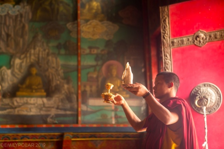 A Buddhist monk holds a torma and ritual object offering during a puja for the deceased at Shechen Monastery in Boudha.