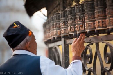 A Nepali man turns the prayer wheels clockwise at Swayambutnath stupa above the Kathmandu Valley of Nepal. Swayambu is an important site for all schools of Buddhists and Hindus alike.