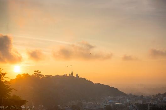 Swayambhu stupa rising along a forest ridge above the crowded urban valley of Kathamandu below.
