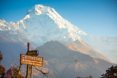 Sign for Chhomorong with the view of Annapurna South from Tadapani in the Annapurna region, Nepal.