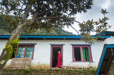 Novice nun stands in a doorway at Thubten Choling monastery in the rural Khumbu, Nepal.